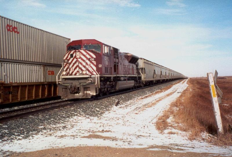 CEFX 106 meets a CP train in Caron, SK (late 1990s)