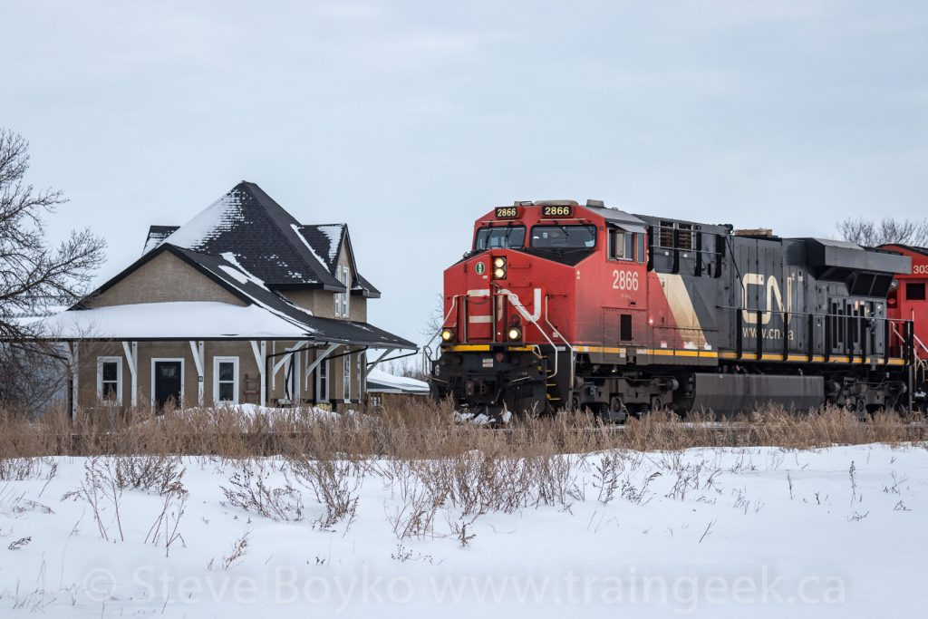 CN 2866 passing the former train station in Elie, MB