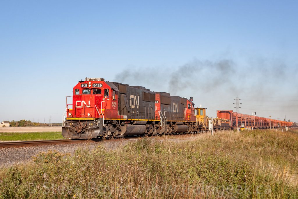 CN 5429 heading up a train with rails...